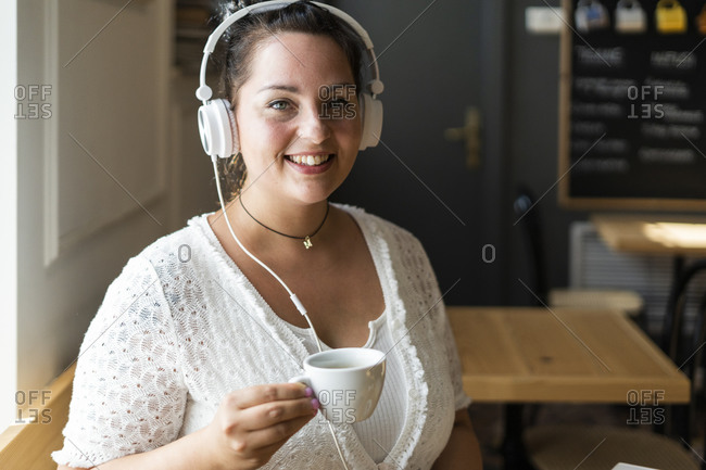 Close-up of smiling young woman holding coffee cup listening music through headphones in cafe
