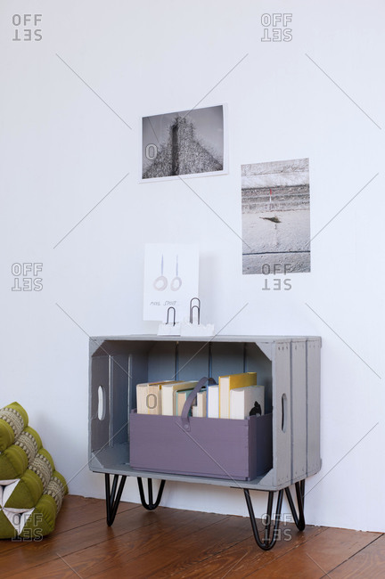 Photographs hanging over DIY bookshelf made of wooden crate