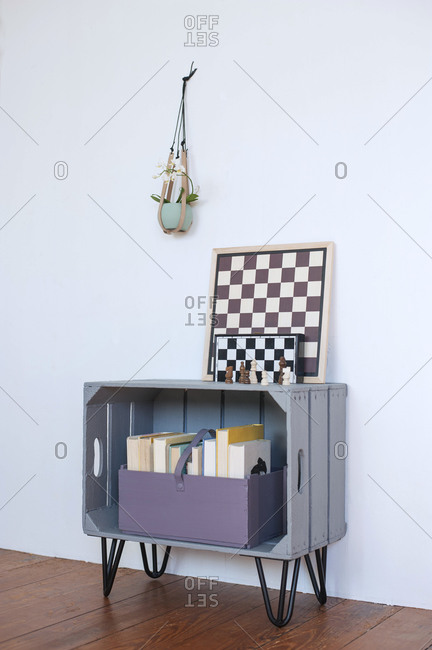 Chess boards lying on top of DIYbookshelf made of wooden crate