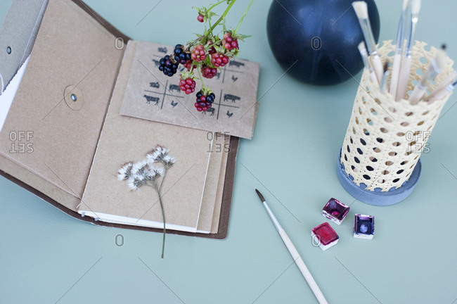 Watercolor paints- dried flowers- note pad and DIY rattan desk organizer with paintbrushes