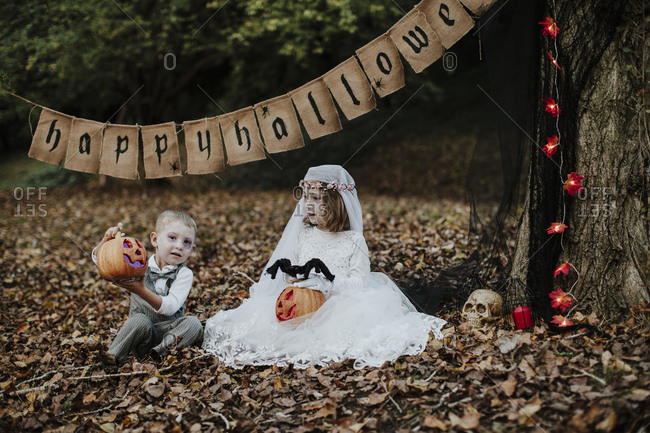 Sibling playing with Halloween toy while sitting in forest