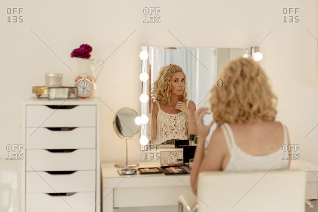 Beautiful woman with blond hair looking in mirror while sitting at beauty spa