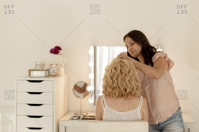 Beautician applying make-up to customer while standing in studio