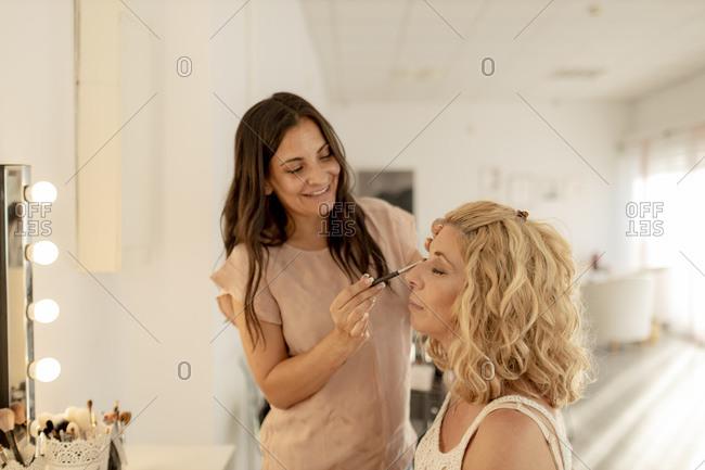 Smiling make-up artist applying eyeshadow to customer in studio