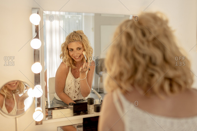 Smiling mid adult woman applying blusher while looking in mirror at studio
