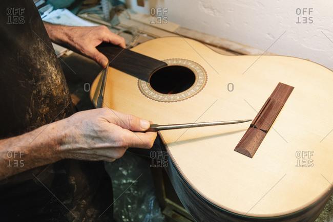 Instrument maker repairing guitar at workshop