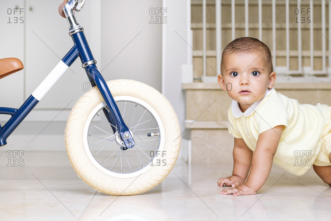 Cute baby crawling on floor at home