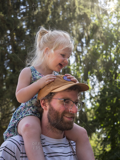 Smiling father carrying daughter on shoulder in public park