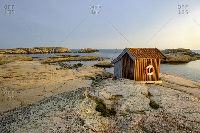 Sweden- Vastra Gotaland County- Grebbestad- Hut on rocky shore of Tjurpannans Nature Preserve at dusk