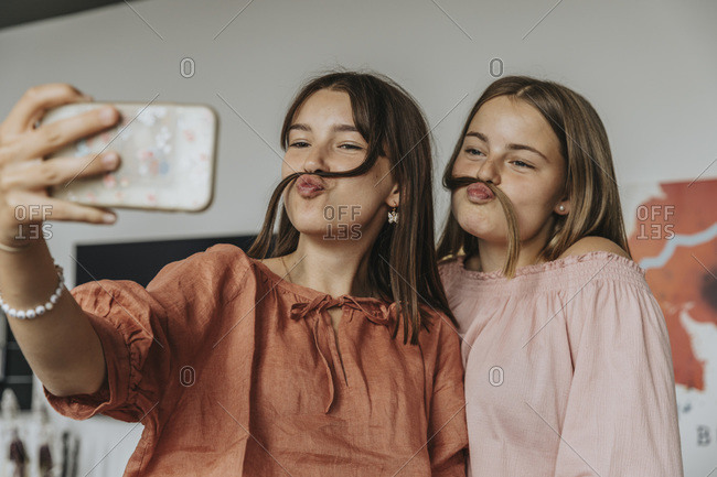 Friends making fake mustache with hair while taking selfie at home