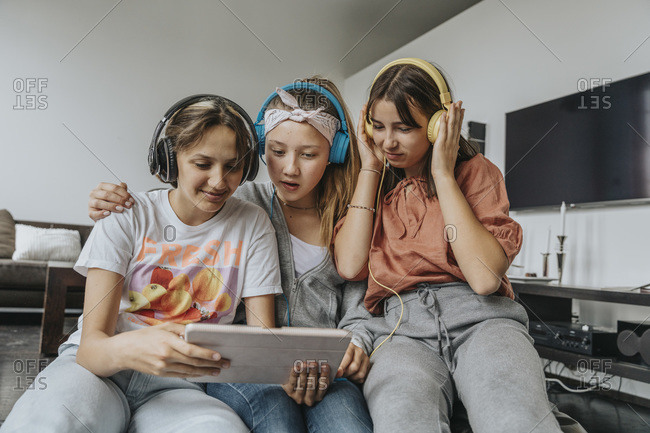 Teenage friends listening music through headphones while using digital tablet at home