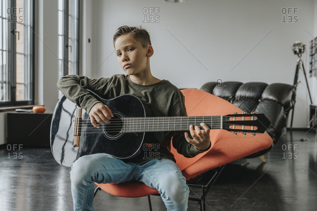 Boy playing guitar while sitting on chair at home