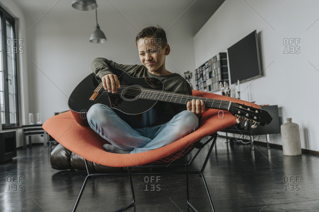 Smiling boy playing guitar while sitting on chair at home