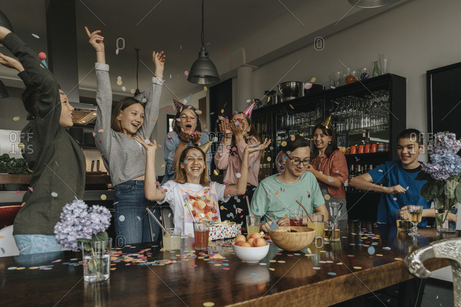 Cheerful friends throwing confetti on birthday girl in party at home