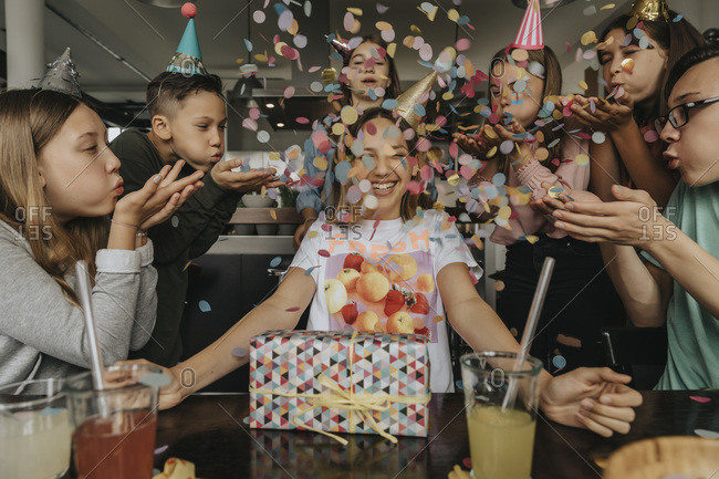 Happy friends throwing confetti on teenage girl sitting with birthday gift at dining table