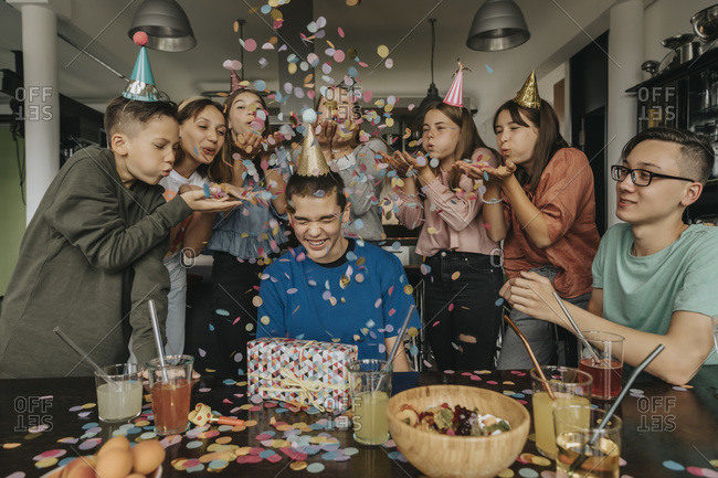 Friends throwing confetti on birthday boy sitting with gift at dining table