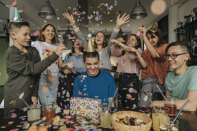 Cheerful friends throwing confetti on birthday boy sitting with gift at dining table