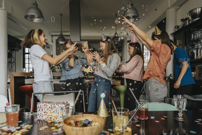 Cheerful friends throwing confetti on birthday girl while celebrating at home