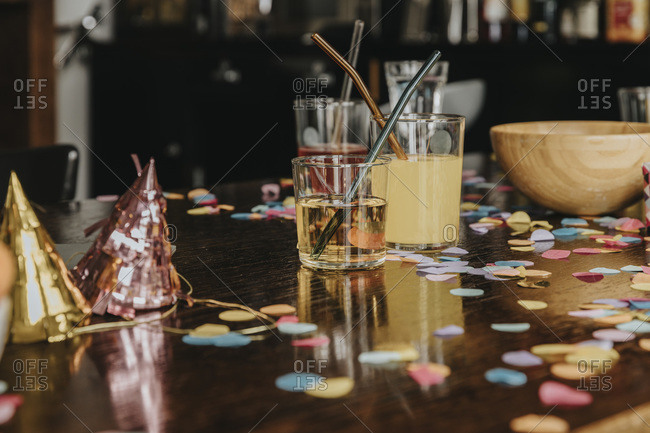 Close-up of drinks with party hats and confetti on dining table at home