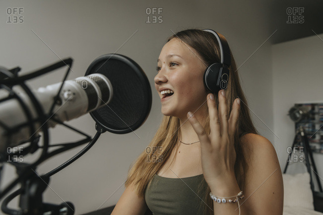 Close-up of happy teenage girl singing against wall in recording studio