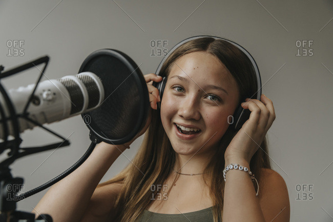 Close-up portrait of happy teenage girl singing against wall in recording studio