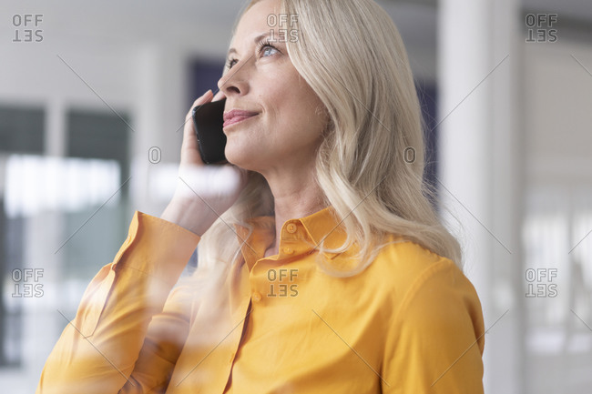 Close-up of businesswoman talking over smart phone in home office seen through window