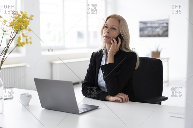 Female entrepreneur with laptop on desk talking over smart phone in home office