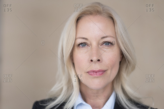 Close-up of confident female entrepreneur with blond hair against wall in office