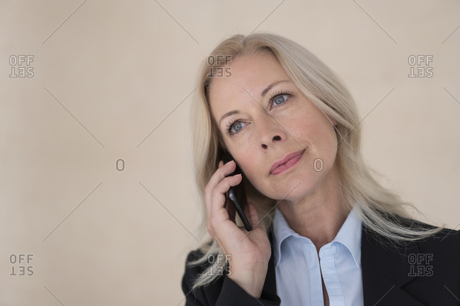Close-up of female entrepreneur talking over mobile phone against wall in office