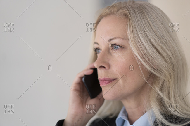 Close-up of female professional talking over mobile phone against wall in office