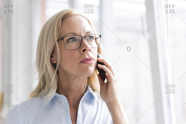 Close-up of female professional talking over smart phone