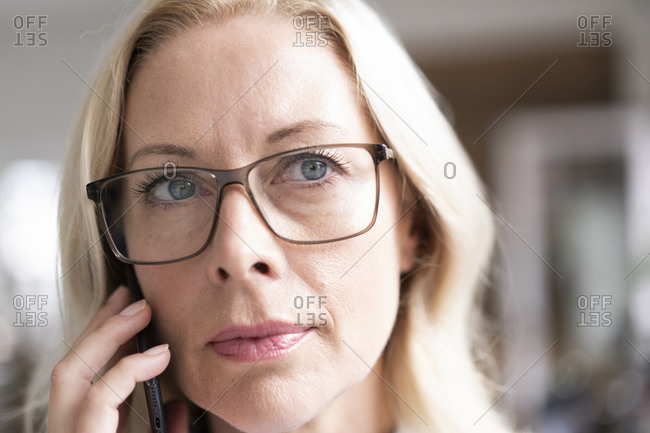 Close-up of female professional wearing eyeglasses talking over mobile phone
