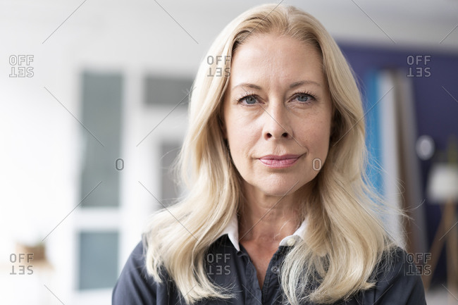 Close-up of confident female professional with blond hair in home office