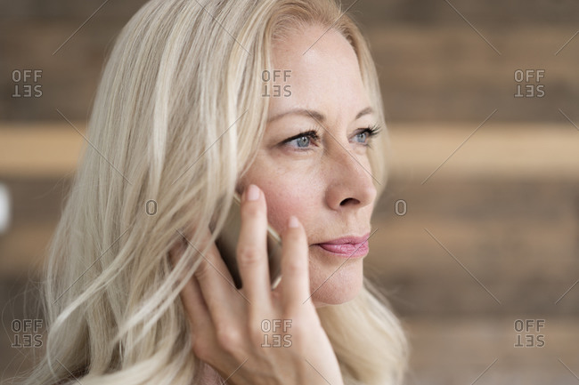 Close-up of confident female professional talking over smart phone looking away
