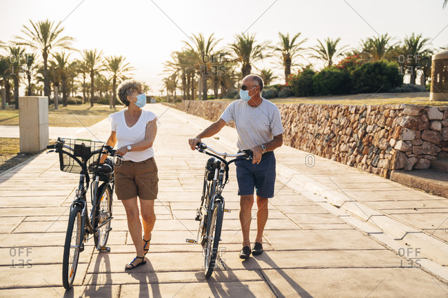 Senior man and woman with face mask talking while walking with cycle at park