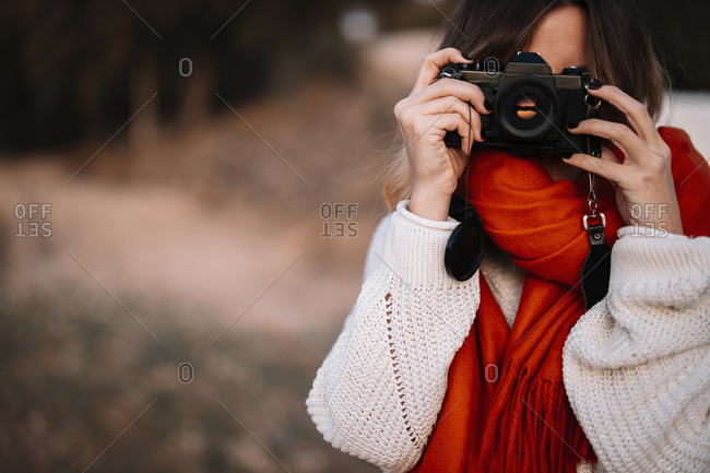 Young woman taking photo from camera while standing in forest