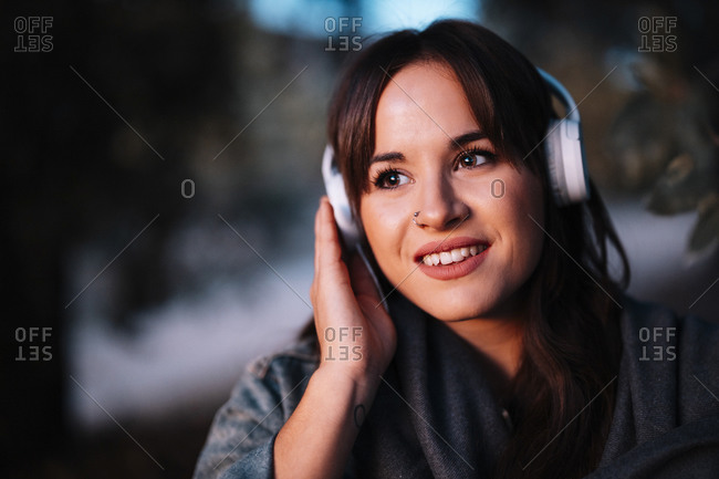 Attractive woman listening to music through headphone in forest