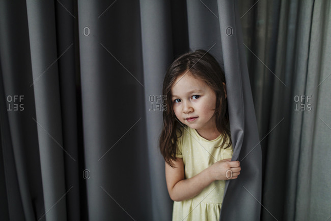 Cute girl standing against gray curtain at home
