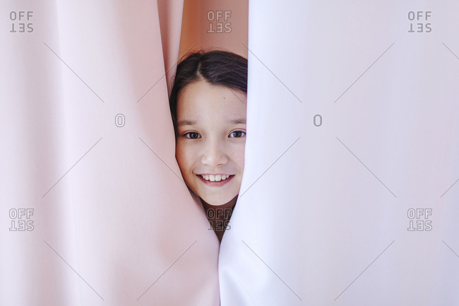 Smiling girl hiding behind curtain at home
