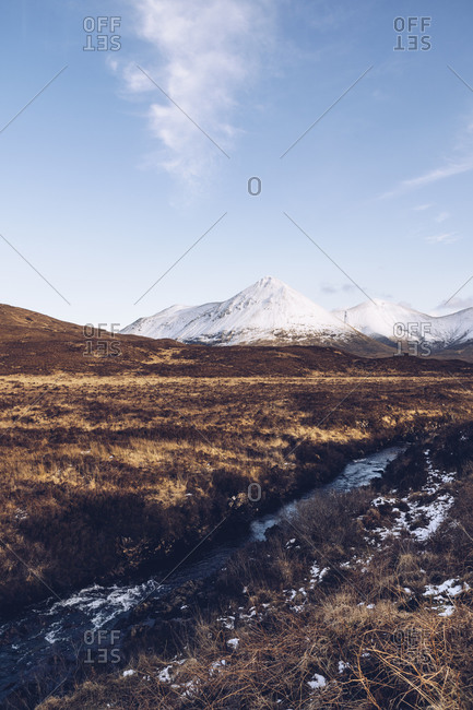 UK- Scotland- River flowing on Isle of Skye in winter with snowcapped mountains in background