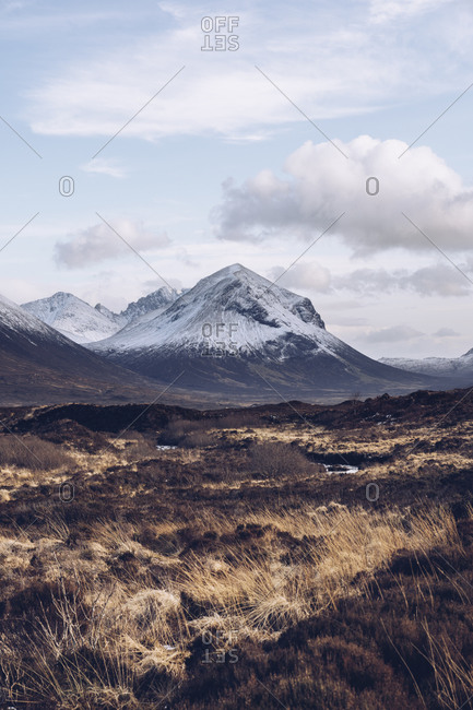 UK- Scotland- Brown grassy landscape of Isle of Skye in winter with snowcapped mountains in background