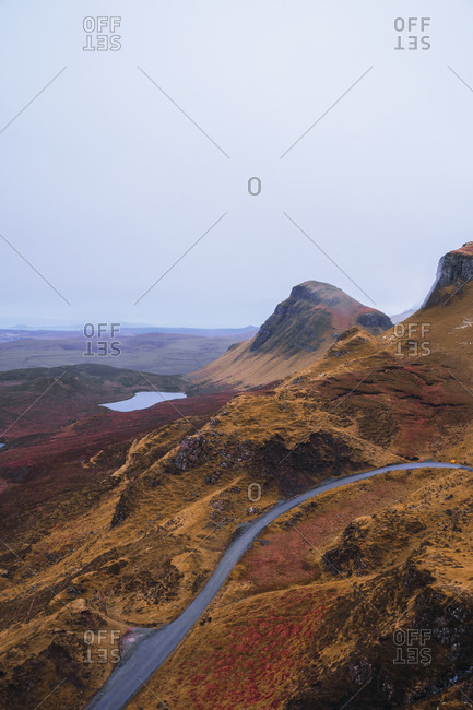 UK- Scotland- Drone view of empty highway stretching along brown mountainous landscape of Isle of Skye with small lake in background