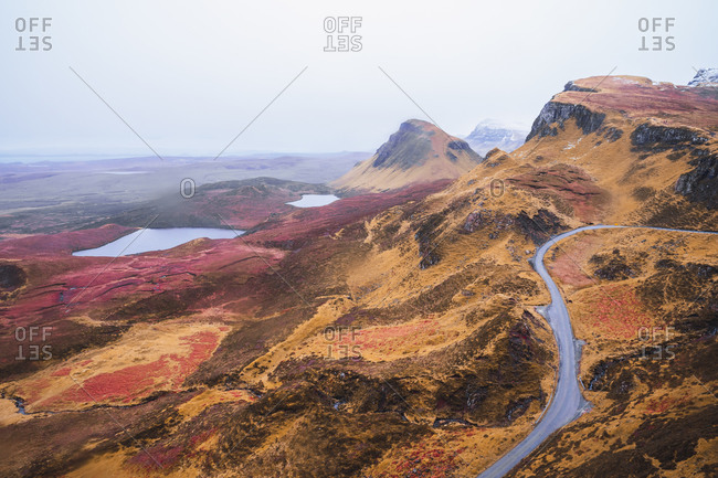 UK- Scotland- Drone view of empty highway stretching along brown mountainous landscape of Isle of Skye with small lakes in background
