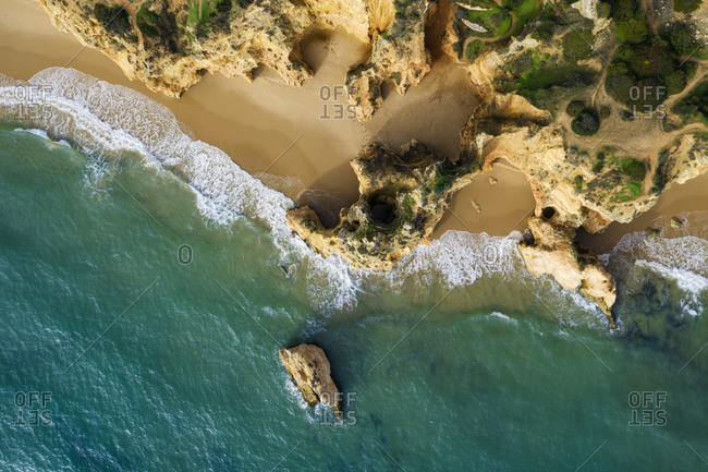 Portugal- Algarve- Alvor- Drone view of sandstone cliffs and beach at Praia dos Tres Irmaos