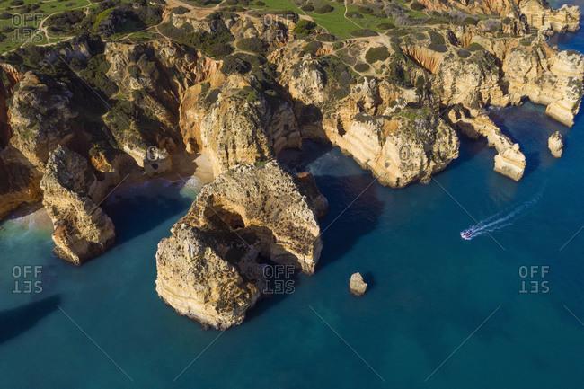 Portugal- Algarve- Lagos- Drone view of motorboat moving toward sea stacks of Ponta da Piedade headland