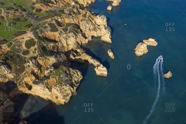 Portugal- Algarve- Lagos- Drone view of motorboat moving past sea stacks of Ponta da Piedade headland