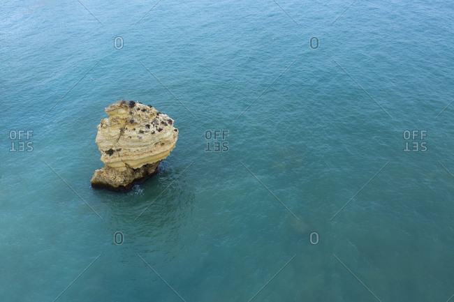 Portugal- Algarve- Lagoa- Drone view of stack rock in turquoise waters of Atlantic Ocean
