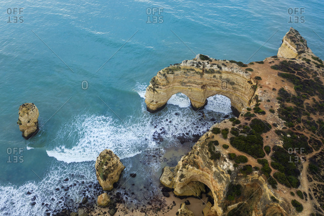 Portugal- Algarve- Lagoa- Drone view of turquoise waters of Atlantic Ocean and coastal rock arch