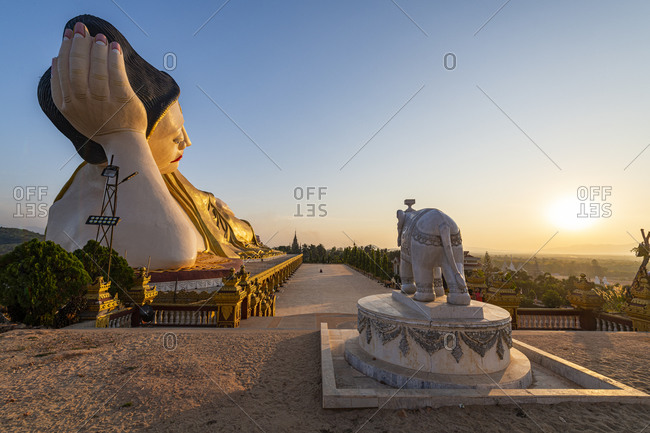 Myanmar- Mon State- Giant statue of reclining Buddha in Pupawadoy Monastery at sunset