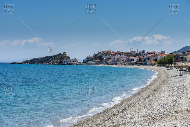Greece- North Aegean- Kokkari- Rocky coastal beach in summer with village in background
